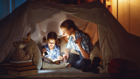 Photo pour reading and family games in children's tent. mother and child daughter with  book and flashlight before going to bed  - image libre de droit