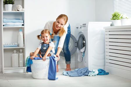 Photo for family mother and child girl little helper in laundry room near washing machine and dirty clothes - Royalty Free Image