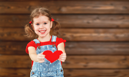 Photo for happy laughing child girl with heart Valentine's Day, wooden background - Royalty Free Image