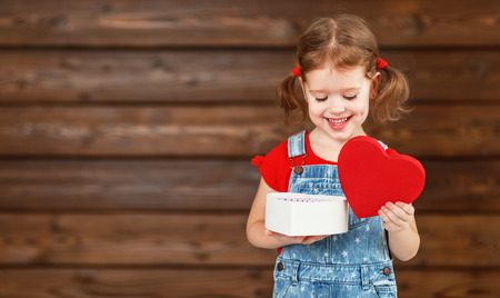 Photo pour happy laughing child girl with gift Valentine's Day, wooden background - image libre de droit