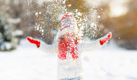 Photo for happy child girl throws up snow on a winter walk - Royalty Free Image