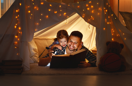 Foto de happy family father and child daughter  reading a book with a flashlight in a tent at home  - Imagen libre de derechos