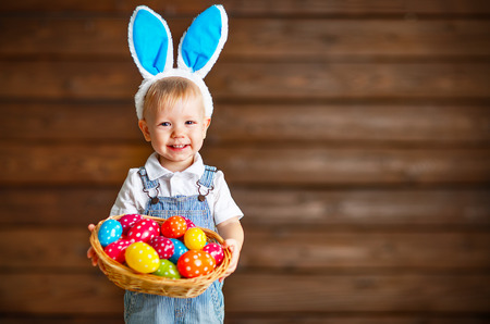 Photo for Happy baby boy in Easter bunny suit with a basket of eggs - Royalty Free Image