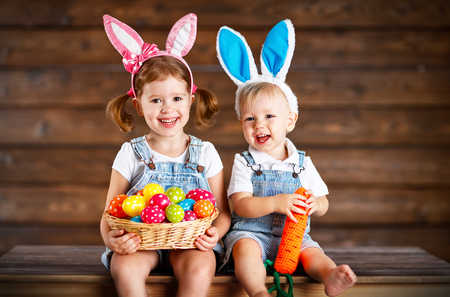 Foto de Happy kids boy and girl dressed as Easter bunnies laughing with basket of eggs on wooden background - Imagen libre de derechos