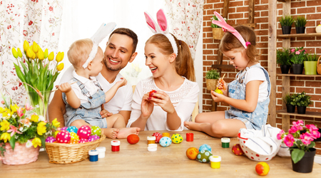 Photo for Happy easter! family mother, father and children having fun paint and decorate eggs for holiday - Royalty Free Image