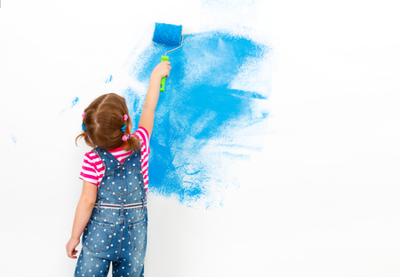 Photo for Repair in the apartment. Happy child girl paints the wall with blue paint - Royalty Free Image