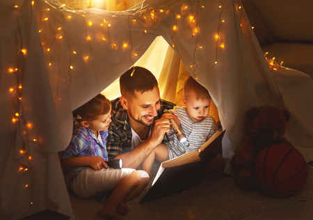Foto de happy family father and children reading a book with a flashlight in a tent at home - Imagen libre de derechos