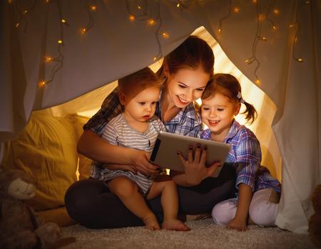 Foto de Happy family mother and children playing in tablet  pc in a tent evening in dark - Imagen libre de derechos