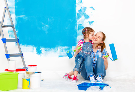 Photo for Repair in the apartment. Happy family mother and child daughter  paints the wall with blue paint - Royalty Free Image
