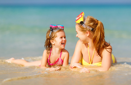 Photo for Happy family mother and chid daughter in masks for swimming on the beach in summer - Royalty Free Image