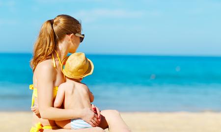 Foto de happy family mother with baby son   on the beach in summer - Imagen libre de derechos