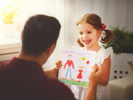 Foto de Father's day. Happy family daughter giving dad a greeting card on holiday - Imagen libre de derechos