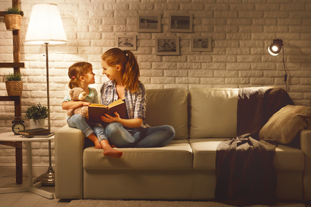 Photo pour Family before going to bed mother reads to her child daughter book near a lamp in the evening - image libre de droit