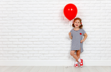 Photo pour Happy funny child girl with a red ball near an empty white brick wall - image libre de droit