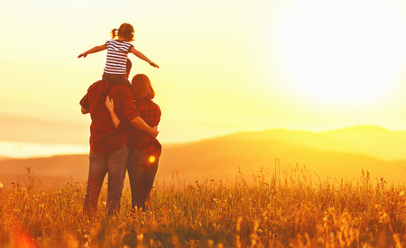 Foto de Happy family: mother father and child daughter on nature  on sunset - Imagen libre de derechos