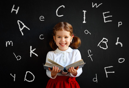 Foto de Happy schoolgirl preschool girl with book near school board blackboard  - Imagen libre de derechos