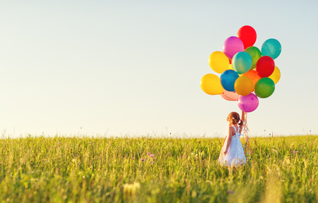 Photo pour Happy cheerful child girl with balloons on meadow at sunset on nature in summer - image libre de droit