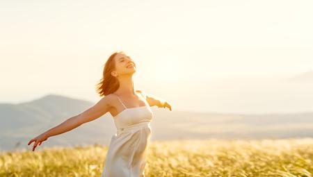 Foto de Happy woman standing with her back on the sunset in nature in summer with open hands - Imagen libre de derechos