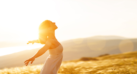 Photo pour Happy woman standing with her back on the sunset in nature in summer with open hands - image libre de droit