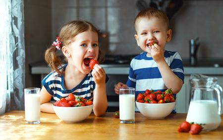 Foto de Happy children girl and boy brother and sister eating strawberries with milk - Imagen libre de derechos