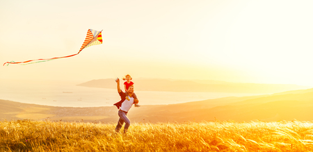 Foto de happy family father and baby daughter run with a kite on meadow - Imagen libre de derechos