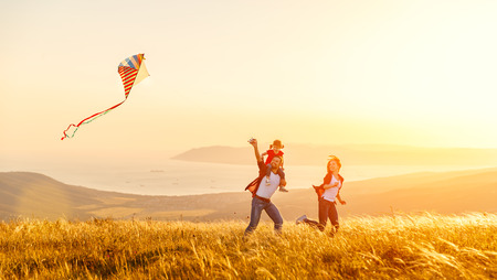 Photo for Happy family father of mother and child daughter launch a kite on nature at sunset - Royalty Free Image