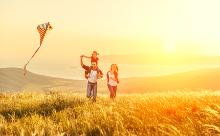 Photo pour Happy family father of mother and child daughter launch a kite on nature at sunset - image libre de droit