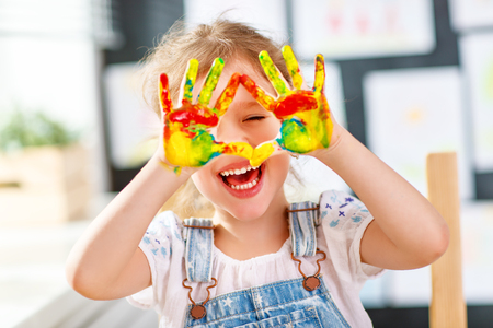 Foto de happy funny child girl draws laughing shows hands dirty with paint - Imagen libre de derechos