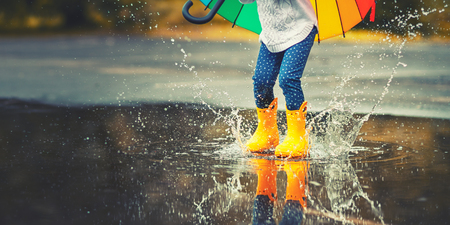 Foto de Feet of child in yellow rubber boots jumping over a puddle in the rain  - Imagen libre de derechos