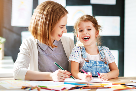 Foto de mother and child daughter draws are engaged in creativity in kindergarten  - Imagen libre de derechos