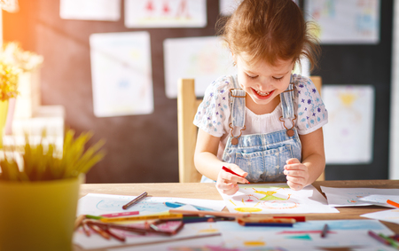 Foto de child  girl draws with colored pencils in kindergarten  - Imagen libre de derechos