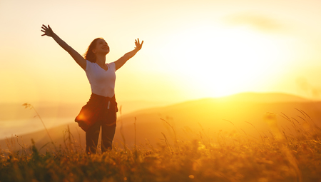 Photo for Happy woman   on the sunset in nature in summer with open hands  - Royalty Free Image