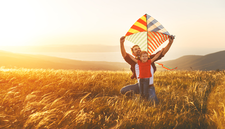 Foto per happy family father and baby daughter launch a kite on meadow - Immagine Royalty Free