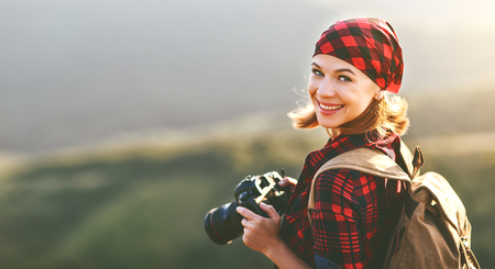 Photo pour Woman tourist photographer with camera on top of a mountain at sunset outdoors during a hike in summer - image libre de droit
