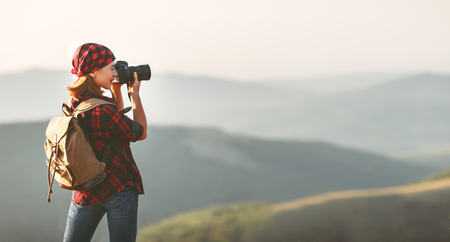 Foto de Woman tourist photographer with camera on top of a mountain at sunset outdoors during a hike in summer - Imagen libre de derechos