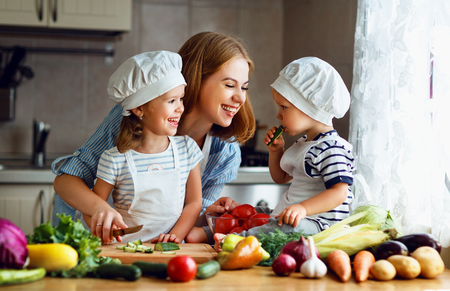 Foto de Healthy eating. Happy family mother and children  prepares   vegetable salad in kitchen  - Imagen libre de derechos
