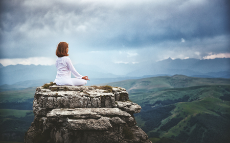 Foto de woman practices yoga and meditates in the lotus position on mountains, peak - Imagen libre de derechos