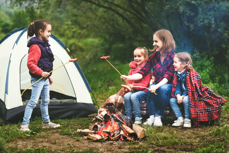 Photo for Happy tourist family on a journey hike. mother and children fry sausages on bonfire near the tent - Royalty Free Image