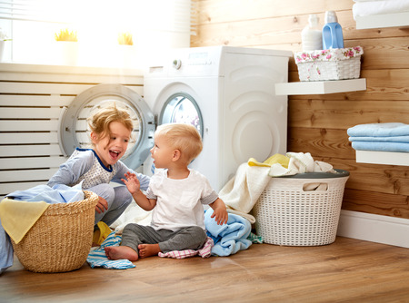 Photo pour Happy children boy and girl in   in the laundry load a washing machine - image libre de droit