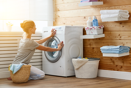 Photo for a Happy housewife woman in laundry room with washing machine    - Royalty Free Image