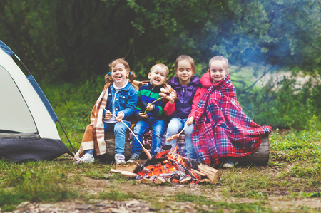 Photo for Children laugh and fry sausages at the stake near a tent in a hike - Royalty Free Image