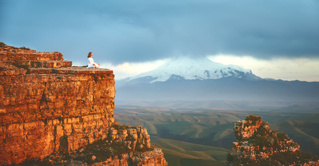 Foto de woman practices yoga and meditates   on mountains, peak - Imagen libre de derechos