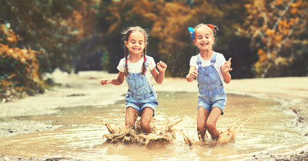 Photo pour Happy funny sisters twins  child by girl jumping on puddles in rubber boots and laughing - image libre de droit