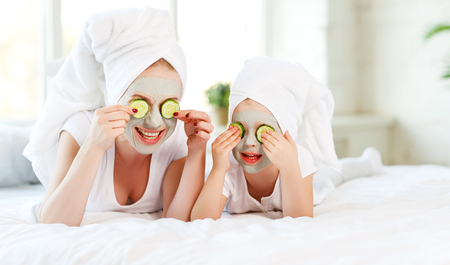 Photo for Happy family mother and child daughter make face skin  mask with towel on head - Royalty Free Image