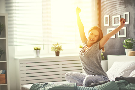 Photo for young happy woman woke up in the morning in the bedroom by the window with her back - Royalty Free Image