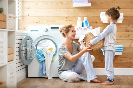 Foto per Happy family mother housewife and child daughter in laundry with washing machine   - Immagine Royalty Free