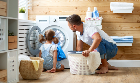 Photo for Happy family man father  householder and child daughter in laundry with washing machine   - Royalty Free Image