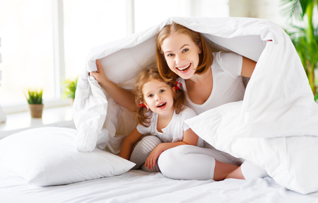 Photo for Happy family mother and child daughter play and laugh in bed - Royalty Free Image