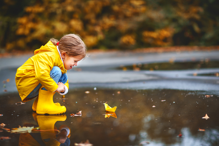 Foto de happy child girl with paper boat in a puddle in   autumn on nature - Imagen libre de derechos