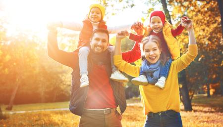 Foto de happy family mother, father and children on an autumn walk in park - Imagen libre de derechos